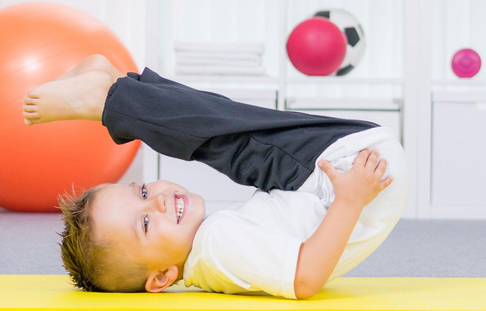 Kleiner junge liegt lachend auf dem Rücken bei einer ergotherapheutischen Übung