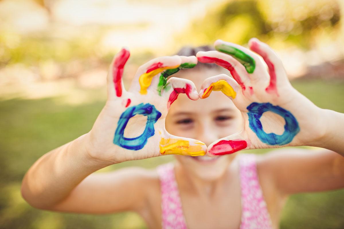 Kind mit bemalten Händen.
